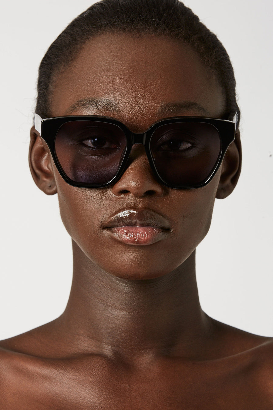 The oversized square frame silhouette with rounded edges features tonal lenses and a subtle logo detail.