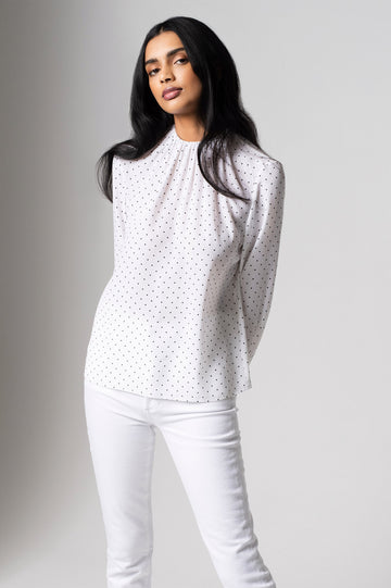 The Crepe de Chine Spot Blouse has full-length sleeves with cuffs, a gathered neckline,