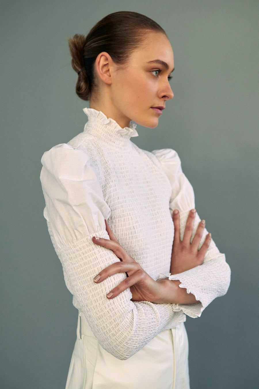 Be a modern day victorian with this fully smocked cotton blouse that features a high neck and puff sleeve