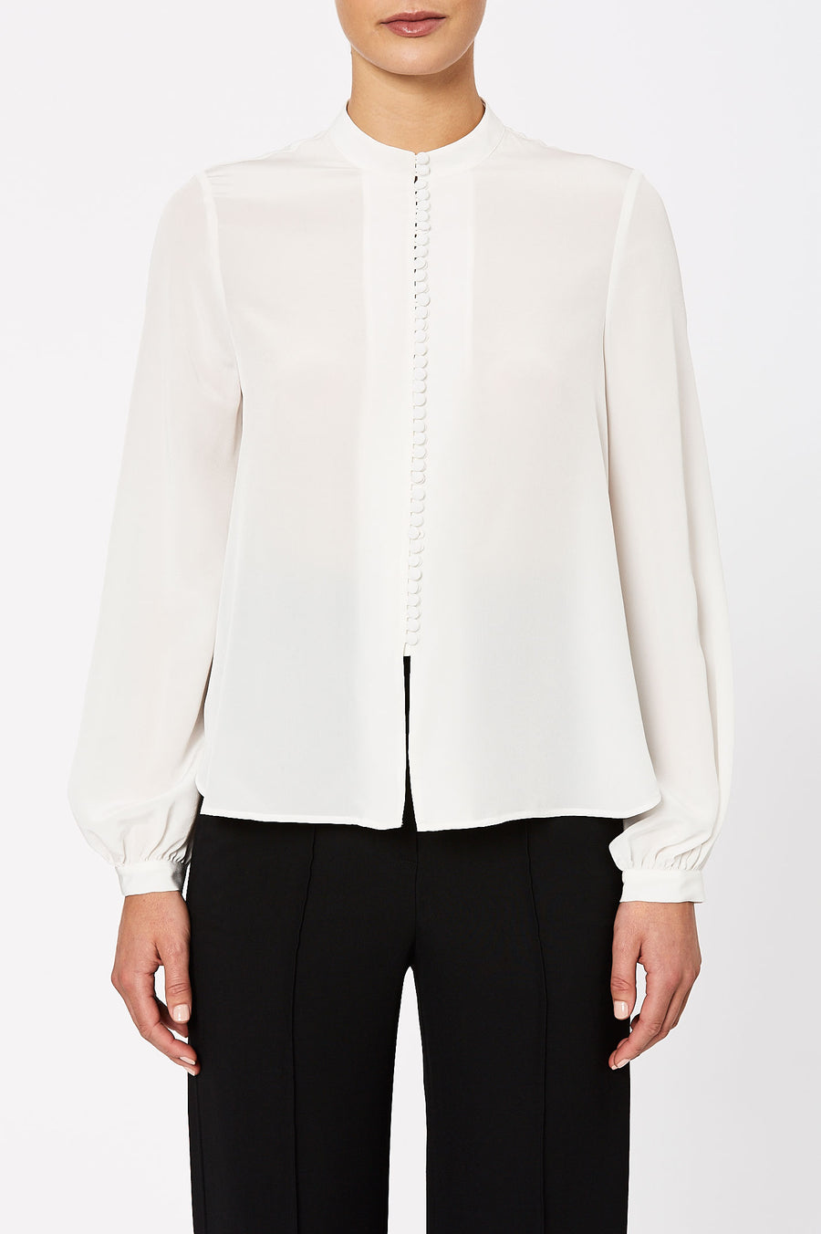 Cut from a luxurious silk, the long sleeved blouse features buttons cascading down from the neckline and long blouson sleeves.