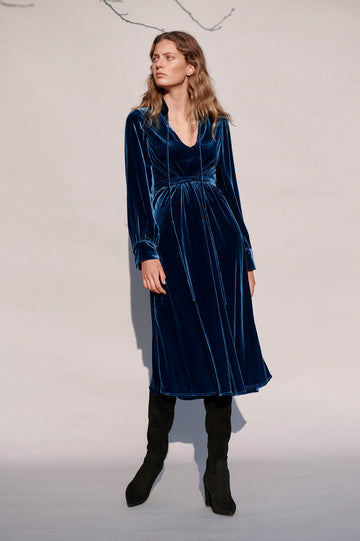 The textured dress features v neckline with delicate tie closure and exaggerated sleeves