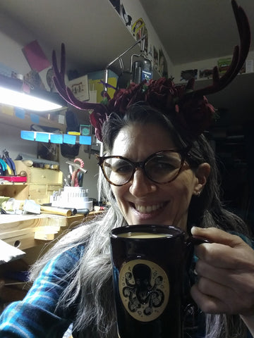 Natalia being silly and drinking coffee at her workbench