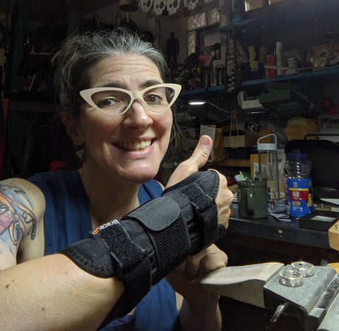 Natalia (a fair skinned, gray haired woman with cat eye glasses, giving a thumbs up with her braced arm.