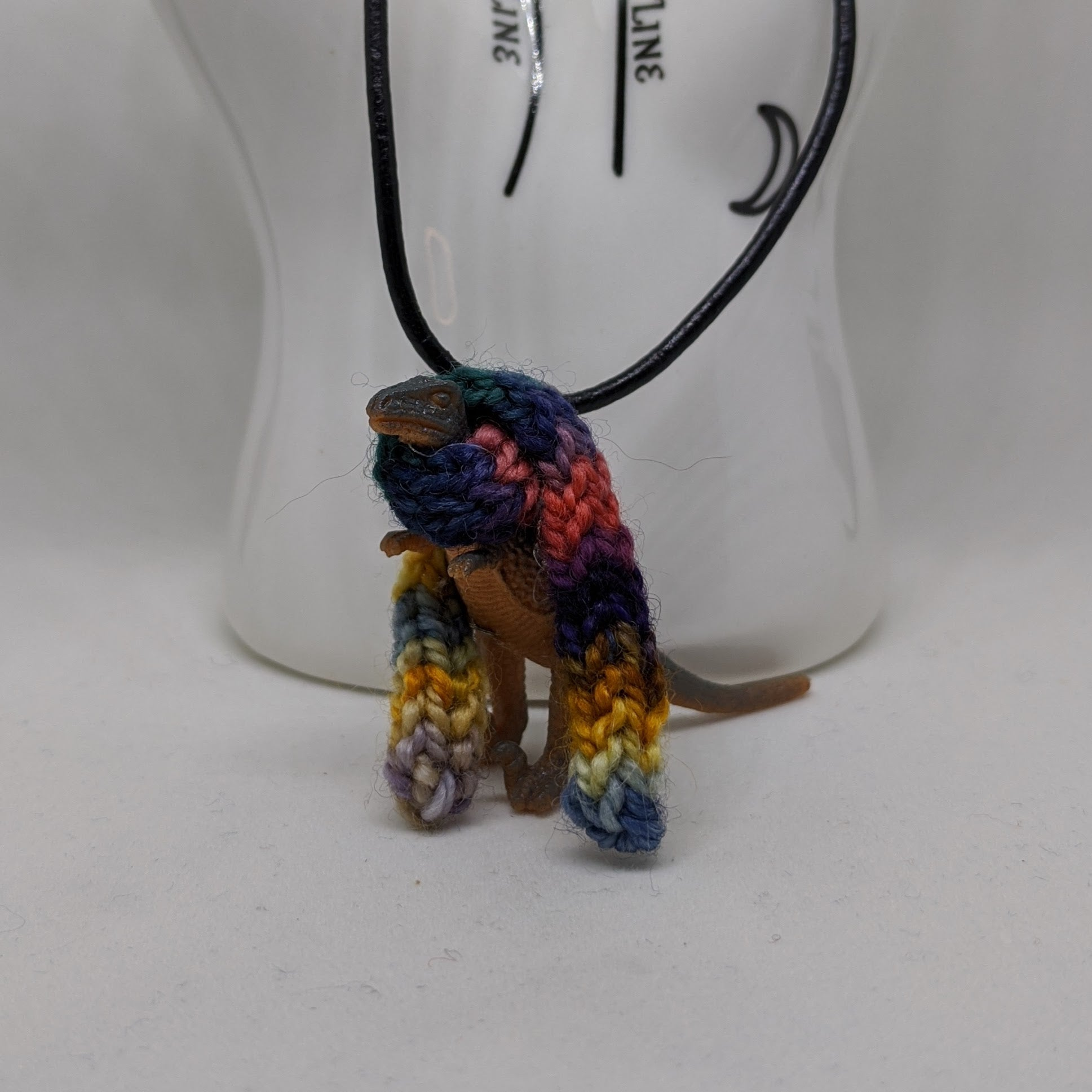 Tan and gray dinosaur wearing a handknit multicolor scarf necklace