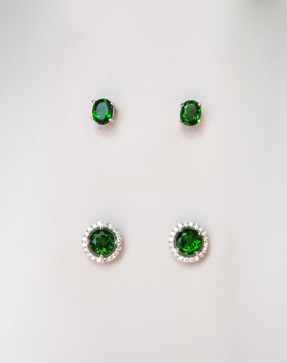 oval emerald stud earrings and round emerald with a diamond halo earring studs