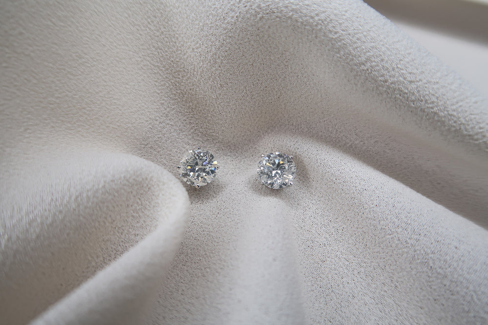4 prong 14k white gold diamond earrings 2 carats sitting on a piece of white silk..
