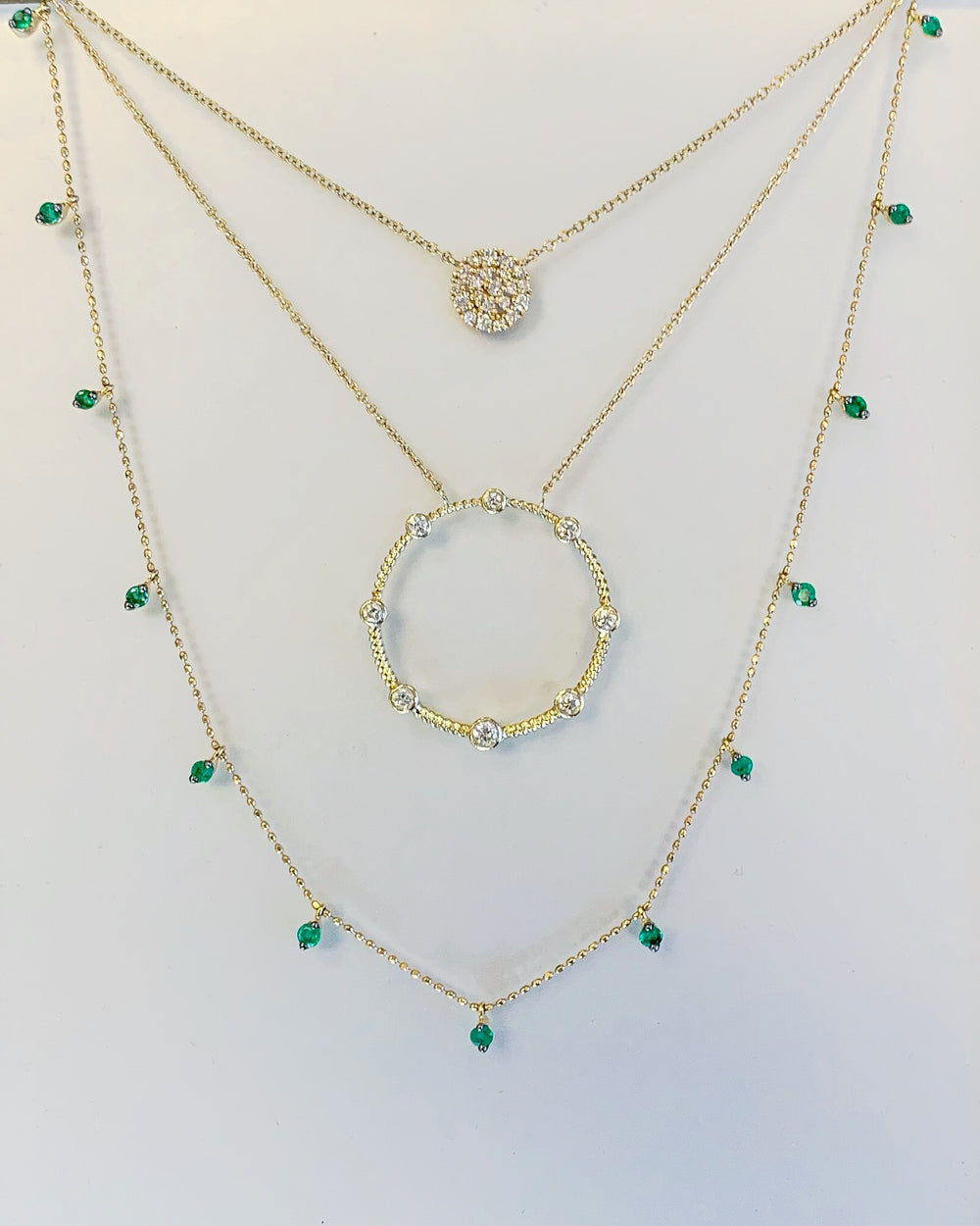3 necklaces layered. yellow gold diamond pavé disk, 14k yellow gold diamond open negative space circle pendant, and 14k yellow gold emerald dangle drop necklace