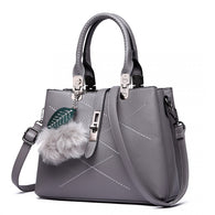 grey handbag with pom pom