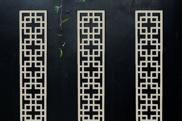 Weatherproof cream trellises made by Screen With Envy. Installed on black wall for a garden wall art feature.