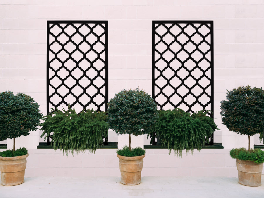 Two black Moroccan inspired privacy screens by Screen With Envy used behind planters