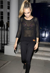 Cara wearing a sweater with a bralette underneath