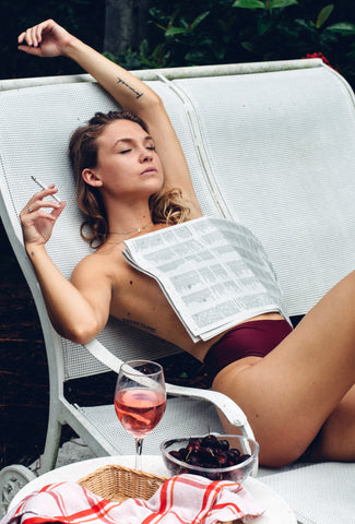 Cam covered by newspaper sipping wine