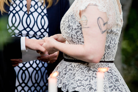 A couple (Kim and Shae) are holding hands behind lit candles. One is wearing a tuxedo and the other is wearing a lacy, sleeveless, ivory and black dress.