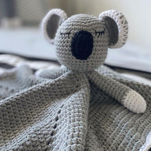 CLose up of COmfirt toy, snuggle blanket in the character of a grey crochet koala