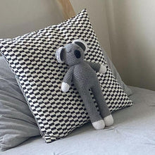 A soft grey koala toy that is hand crochet with a sleepy eyes and a black nose.