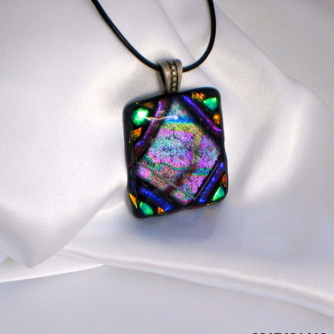 This is a slightly angled view of pendant with a black leather cord necklace.