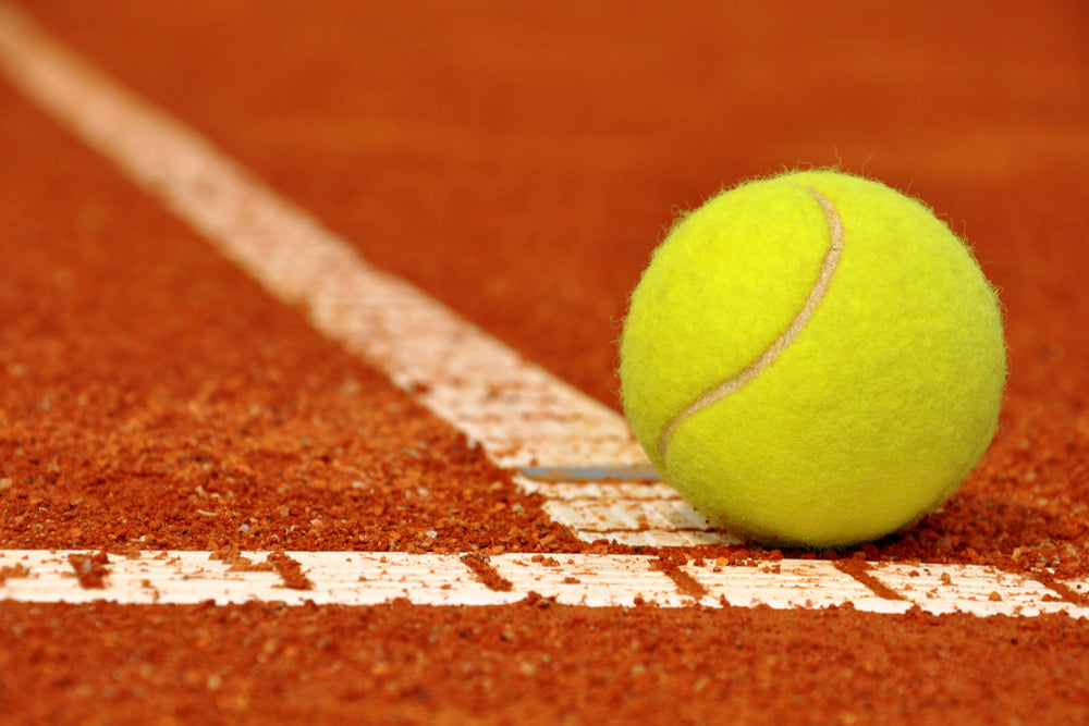 Yellow tennis ball on line of red clay tennis court