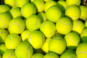 Lots of tennis balls in a pile