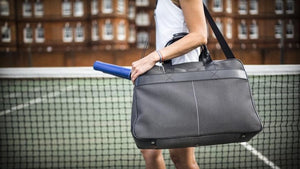 Epirus 24 Hour Bag with electric blue grip covers on tennis court