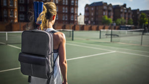 Epirus backpack with two rackets and electric blue grip covers on tennis court