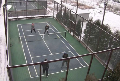 Platform tennis court with 4 players in the middle of a point