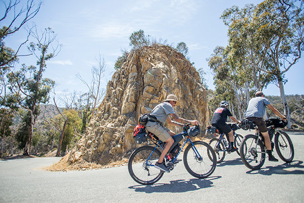 three men riding bicycles up a hill