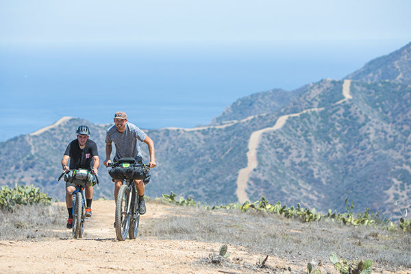 two men riding bicycles up a gravel trail