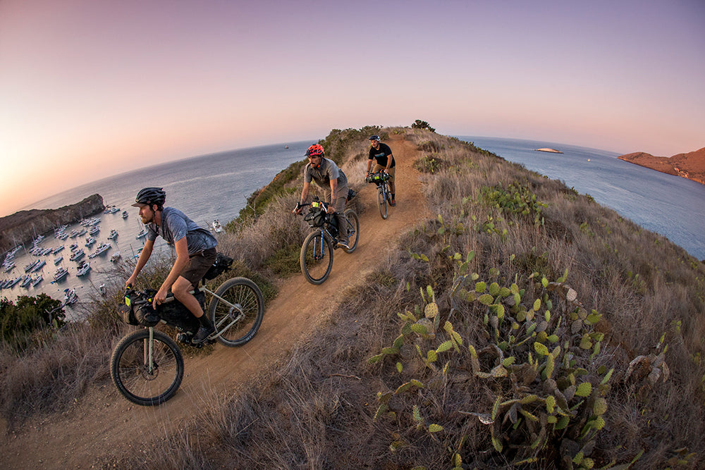three men riding bicycles on a gravel trail  at sunset