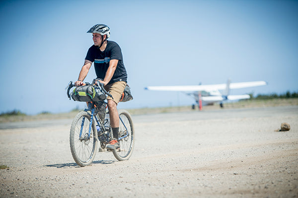 man on bicycle near air strip