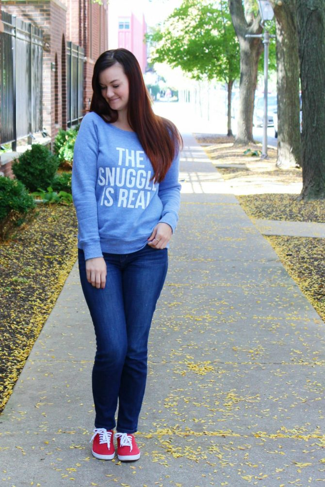 "Blogger, Lindzi Shanks, pairs a graphic sweater that says ""The Snuggle is Real"" with dark wash skinny jeans and red sneakers."