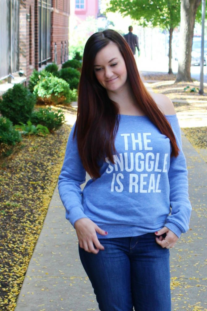 "Lindzi Shanks of The Trendy Sparrow wears an off the shoulder blue graphic sweater that says ""The Snuggle is Real"""