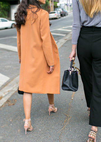 women in work clothes wearing orange coat, grey knit top and black pants on their way to the office