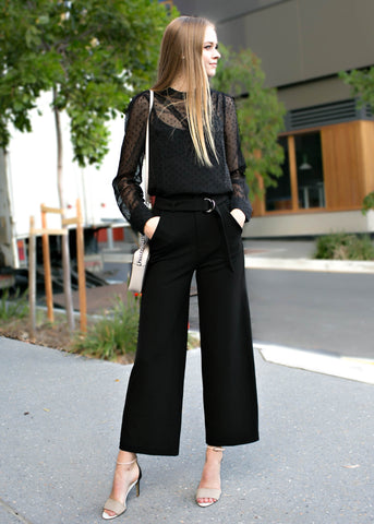 Woman in black work pants and sheer blouse