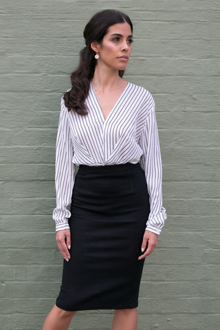 Front view of black work skirt and white striped blouse