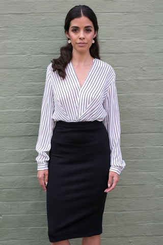 Front view of long sleeve crossover white work blouse with stripes and black pencil skirt