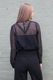 Back view of black sheer work blouse and black pants