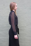 Side view of black sheer work blouse and black pants