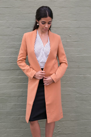 Front view of orange long sleeve collarless work coat