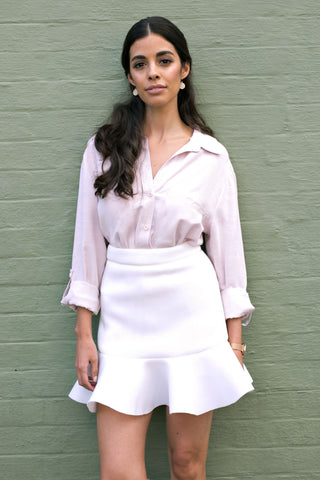 Front view of short white work skirt with flared hem and pink blouse