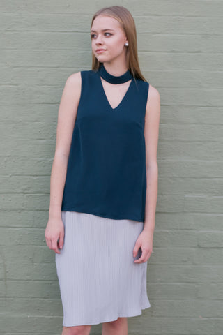 Front view of dark green choker style v neck sleeveless work top and grey skirt