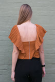 Back view of burnt orange work blouse with frilled sleeves and black pants