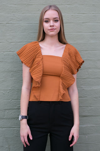 Front view of burnt orange work blouse with frilled sleeves and black pants