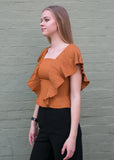 Side view of burnt orange work blouse with frilled sleeves and black pants