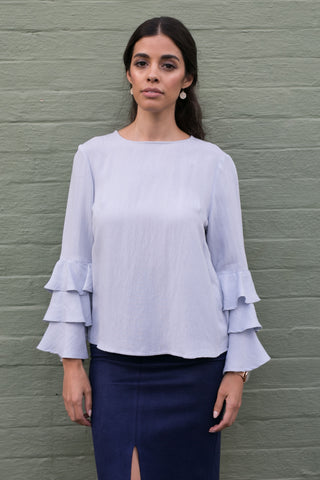 Front view of blue long sleeve top with tiered bell sleeves