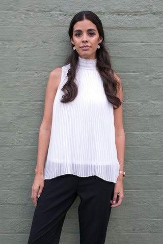 Front view of white pleated high neck sleeveless work top with black pants