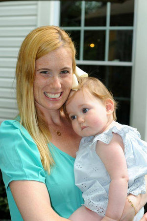 Picture of Jessica, co-founder of unique toddler clothing brand Worthy Threads, holding her baby
