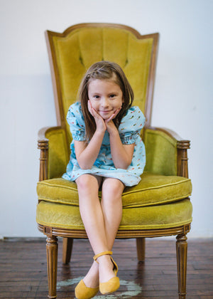 Girl wearing Puff sleeve dress in swimmers print sitting in chair looking at camera.  Puff sleeve dress is featured in Easter Gift guide by Worthy Threads, unique toddler clothing brand.
