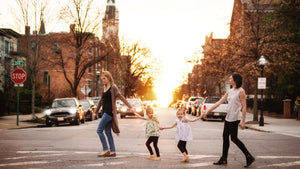 Two moms and two kids walking across city street Golding hands. Image for Worthy Threads, a unique toddler clothing brand.