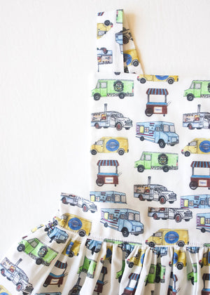 Close up of girls pinafore dress featuring food trucks.  First custom print by Worthy Threads, a unique toddler clothing brand.