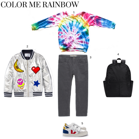 kids outfit featuring multi tie dye raglan, grey corduroys, silver bomber jacket with patches, black backpack and white sneakers with red and green.